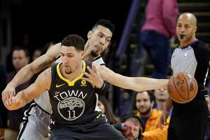 Danny Green (14) goes for the ball while defending against Klay Thompson (11) in the first half as the Golden State Warriors played the San Antonio Spurs at Oracle Arena in Oakland, Calif., on Saturday, February 10, 2018.