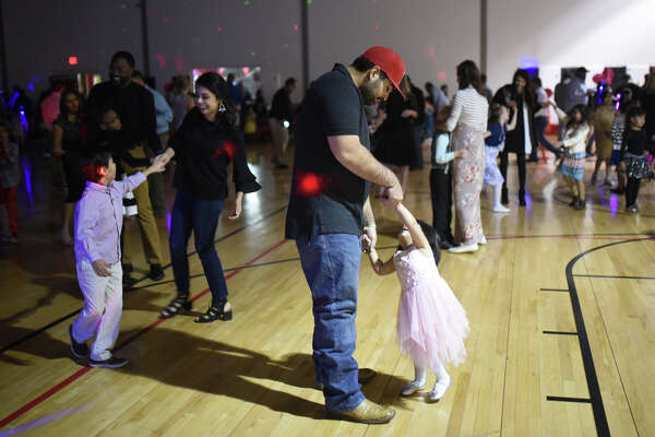 From left, Cristiano, age 7, dances with Anacani Rodriguez, and Caroline, age 2, dances with Gerardo Rodriguez during the Little Sweethearts Dance featuring dancing and games Feb. 10, 2018 at the YMCA. James Durbin/Reporter-Telegram