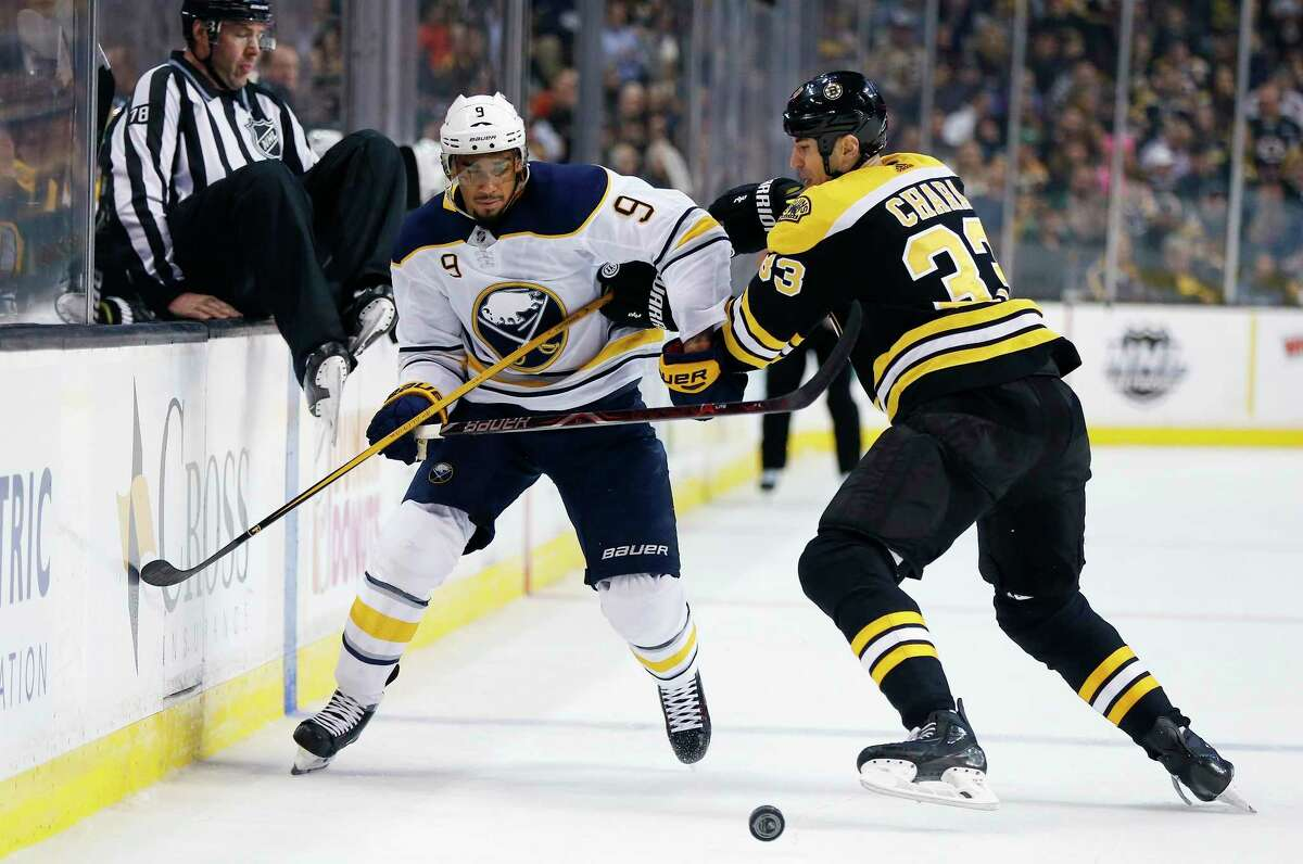 Boston Bruins' Zdeno Chara (33), of Slovakia, battles Buffalo Sabres' Evander Kane (9) for the puck during the first period of an NHL hockey game in Boston, Saturday, Feb. 10, 2018. (AP Photo/Michael Dwyer)