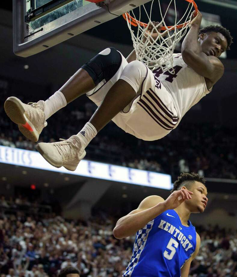 Texas A&M forward Robert Williams (44) hangs from the rim after dunking over Kentucky forward Kevin Knox (5) during the first half of an NCAA college basketball game Saturday, Feb. 10, 2018, in College Station, Texas. (AP Photo/Sam Craft) Photo: Sam Craft, FRE / AP