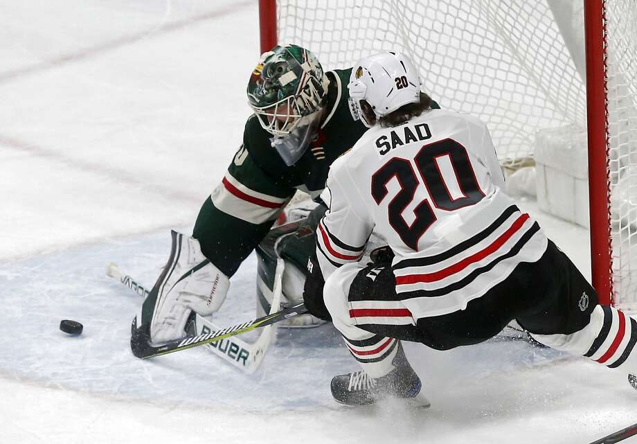 Minnesota goalie Devan Dubnyk stops a shot by Chicago's Brandon Saad (right) in the first period. Dubnyk made a season-high 44 saves in the shutout. Photo: Jim Mone, Associated Press