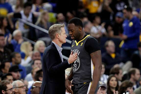 Steve Kerr pats Draymond Green (23) on the chest as he comes out of the game late in the second half as the Golden State Warriors played the San Antonio Spurs at Oracle Arena in Oakland, Calif., on Saturday, February 10, 2018.