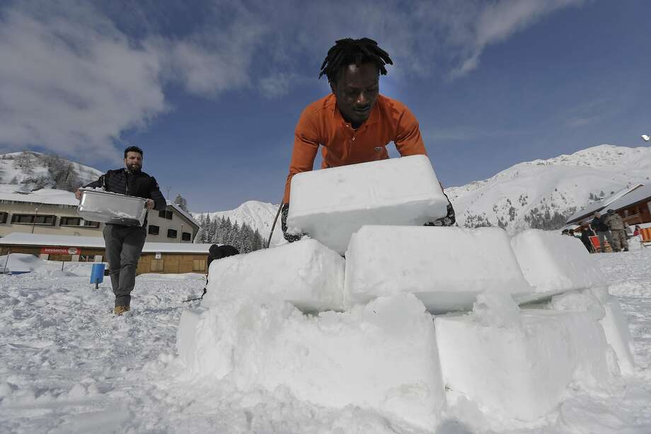 Omar Kanteh (right) of Gambia places a block of compressed snow as he helps construct an igloo with Davide Midali in San Simone di Valleve, near Bergamo in northern Italy. Photo: Luca Bruno, Associated Press