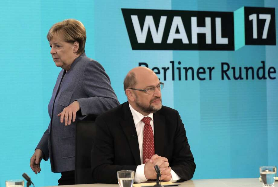 German Chancellor Angela Merkel, head of the Christian Democratic Party, passes by her challenger Martin Schulz, head of the Social Democratic Party, prior to a TV talk. Schulz, the leader of Germany's center-left Social Democrats, said Feb. 9, 2018, he is giving up on plans to become the countrys foreign minister amid turbulence in his party following a coalition deal withMerkel's conservatives. Photo: Gero Breloer, Associated Press