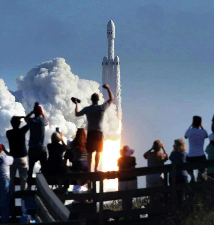 The crowd cheers the launch Tuesday of the SpaceX Falcon Heavy rocket at Cape Canaveral. The launch pad was the same one used by NASA narly 50 years ago for the Apollo 11 moon mission. (Joe Burbank /Orlando Sentinel via AP)