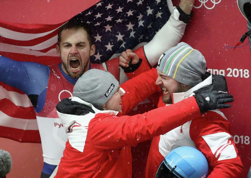 PYEONGCHANG-GUN, SOUTH KOREA - FEBRUARY 11: David Gleirscher of Austria is congratulated by a teammates after winning gold while Chris Mazdzer of the United States celebrates in the background after he won silver in the Luge Men's Singles on day two of the PyeongChang 2018 Winter Olympic Games at Olympic Sliding Centre on February 11, 2018 in Pyeongchang-gun, South Korea.