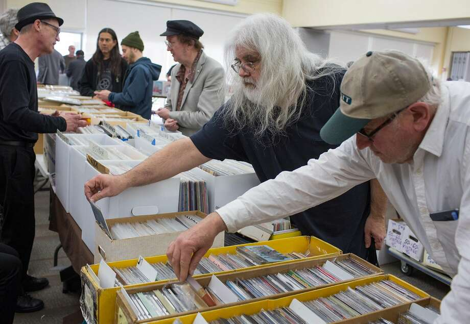 Rory Musil lifts an album from the back of a box as he and Larry Rosenbloom look through music at the KUSF.org Rock 'n' Swap meet at University of San Francisco, which drew hundreds of fans and vendors. Photo: Brian Feulner, Brian Feulner, Special To The Chronicle