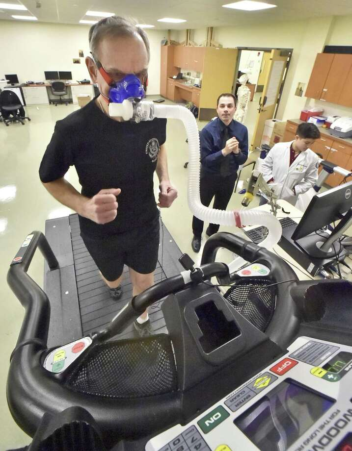 Lewis J. Nescott, Jr. runs on a treadmill at Quinnipiac University's Biomechanics Lab as associate professor Tom Martin and medical student Katherine Woolley observe. Photo: Peter Hvizdak / Hearst Connecticut Media / New Haven Register