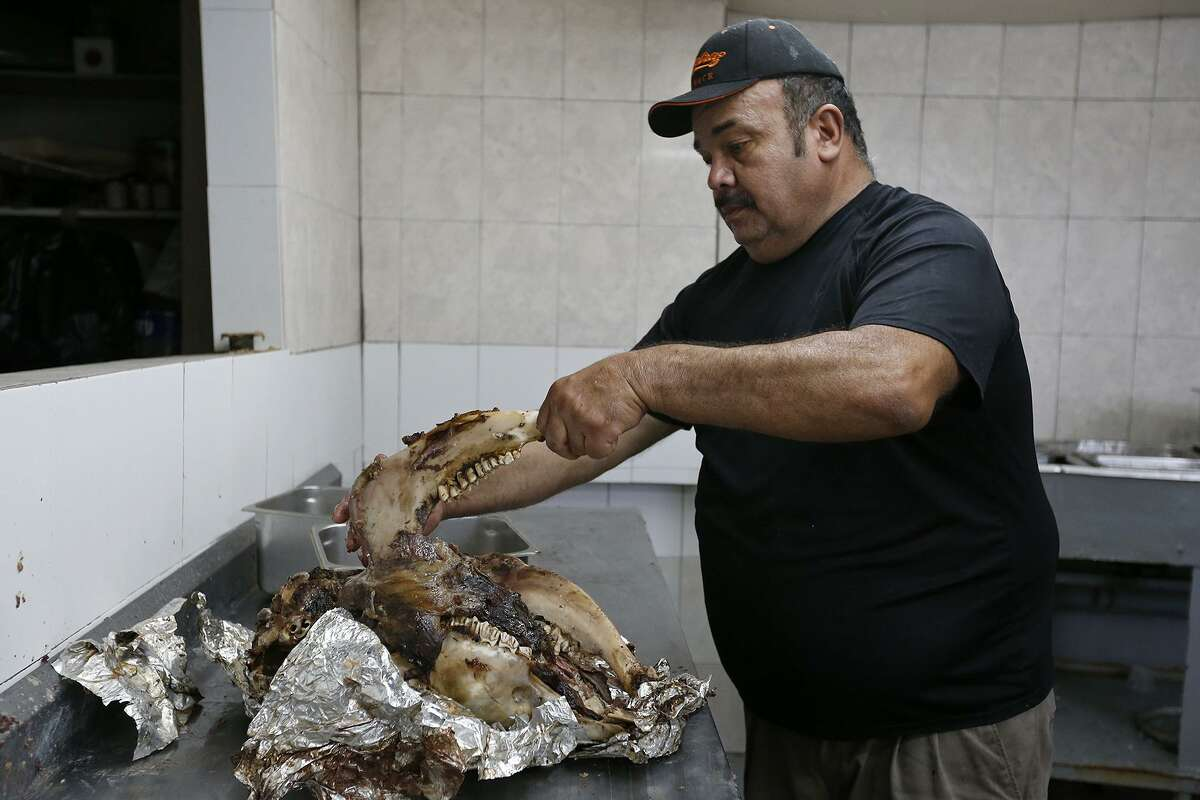 Vera's Backyard Bar-B-Que owner Armando Vera, 57, removes the jaw bone from the calf head after smoking Friday Jan. 26, 2018 at the restaurant in Brownsville, Tx.