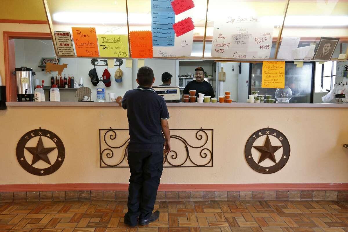 Chris Coello Jr. (left) orders food from Vera's Backyard Bar-B-Que owner Armando Vera, 57, (center) Saturday Jan. 27, 2018 at the restaurant in Brownsville, Tx.
