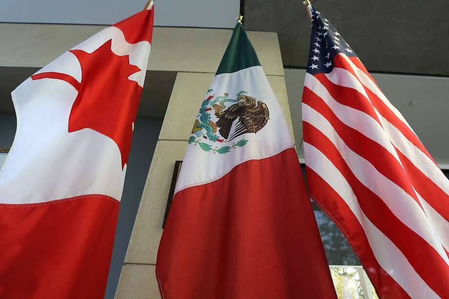 """(FILES) This file photo taken on September 24, 2017 shows the Mexican, US and  Canadian flags in the lobby where the third round of the NAFTA renegotiations took place in Ottawa, Ontario. Canada announced on January 23, 2018 it will sign on the Trans Pacific Partnership, moving to diversify its trade relationships  as Canadian, US and Mexican negotiators kicked off a sixth round of talks on a 1994 free trade pact that Washington has threatened to dump. Canada had initially balked at joining the proposed TPP last year, acting as the main holdout in negotiations after US President Donald Trump decided in early 2017 to go it alone under his """"America First"""" policy.  / AFP PHOTO / Lars HagbergLARS HAGBERG/AFP/Getty Images Photo: LARS HAGBERG, AFP/Getty Images"""