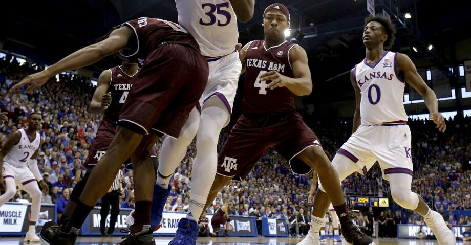 Kansas' Udoka Azubuike (35) looks to pass the ball as he is pressured by Texas A&M's Jay Jay Chandler (0) and JJ Caldwell (4) during the first half of an NCAA college basketball game Saturday, Jan. 27, 2018, in Lawrence, Kan. (AP Photo/Charlie Riedel) Photo: Charlie Riedel/Associated Press