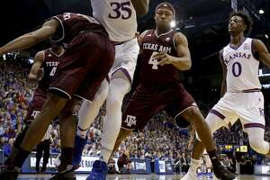 Kansas' Udoka Azubuike (35) looks to pass the ball as he is pressured by Texas A&M's Jay Jay Chandler (0) and JJ Caldwell (4) during the first half of an NCAA college basketball game Saturday, Jan. 27, 2018, in Lawrence, Kan. (AP Photo/Charlie Riedel)