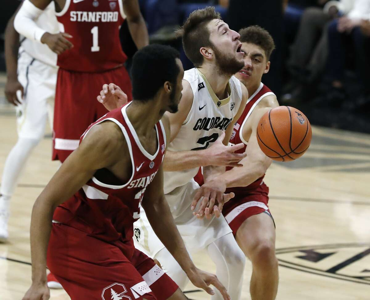 Colorado forward Lucas Siewert, center, is fouled as he goes up for a basket between Stanford forwards Trevor Stanback, front, and Reid Travis in the second half of an NCAA college basketball game Sunday, Feb. 11, 2018, in Boulder, Colo. Colorado won 64-56. (AP Photo/David Zalubowski)