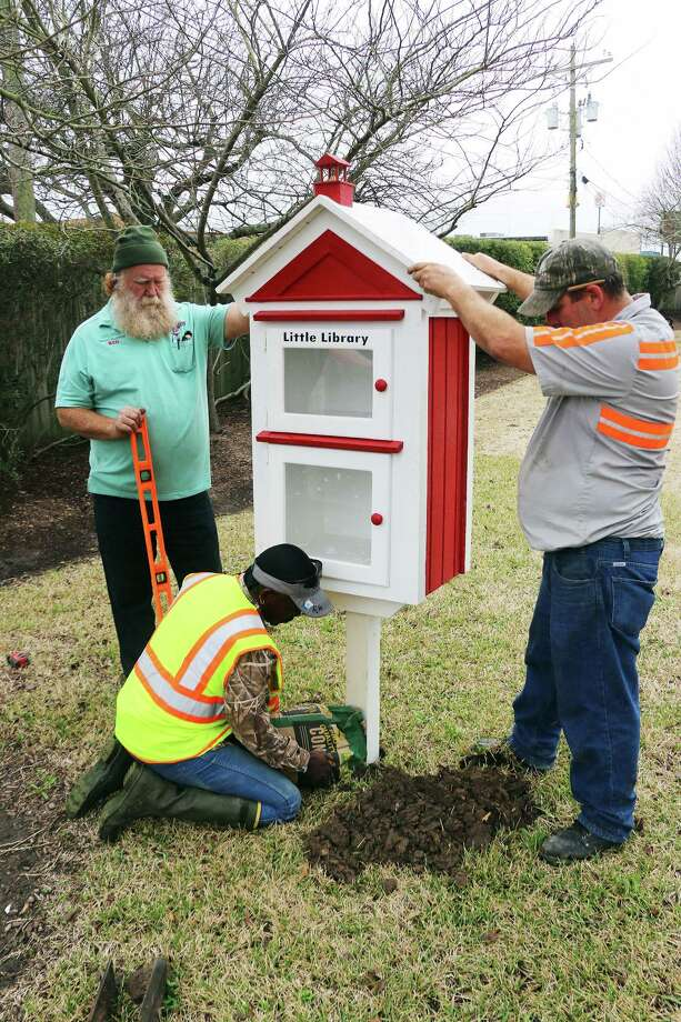 City workers dug a hole and used a level to assure the new My Little Library in the park next to city hall was set properly before concreting it into the ground. Photo: David Taylor