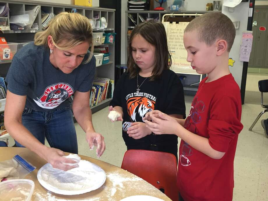Glen Carbon Elementary school second-grade teacher Michelle Herman helps Olivia Cox and Stephen Otten create dough for the land-forms project. Photo: Julia Biggs
