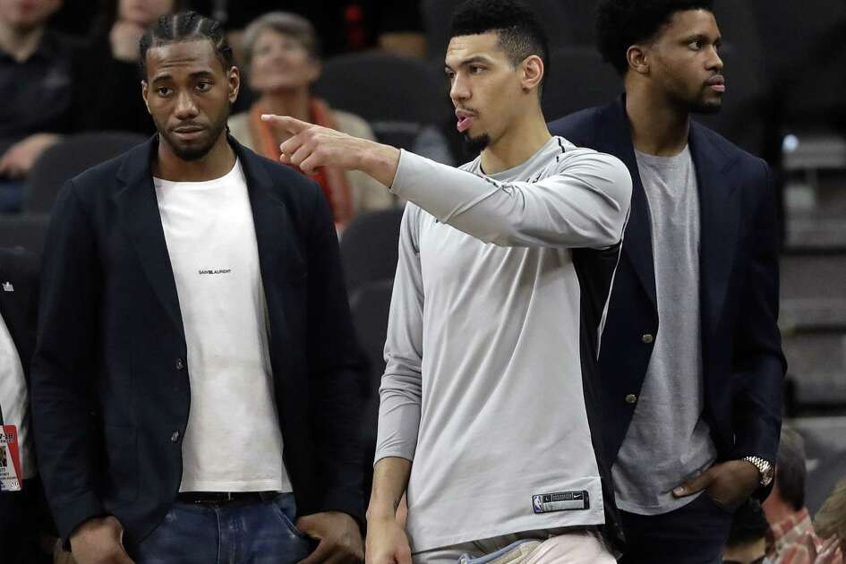 San Antonio Spurs guard Danny Green, center, stands at the bench with injured teammates Kawhi Leonard, left, and Rudy Gay, right, during the second half of an NBA basketball game against the Indiana Pacers, Sunday, Jan. 21, 2018, in San Antonio. Indiana won 94-86. (AP Photo/Eric Gay)