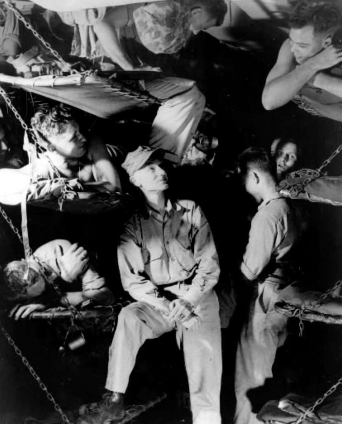 American war correspondent Ernie Pyle, center, talks with Marines below decks on a U.S. Navy transport while en route to the invasion of Okinawa during World War II, in this March 1945 file photo. Pyle was killed on April 18, 1945, by Japanese machine-gun fire on the island of Ie Shima in the southwestern Pacific Ocean near Okinawa. (Associated Press archive)
