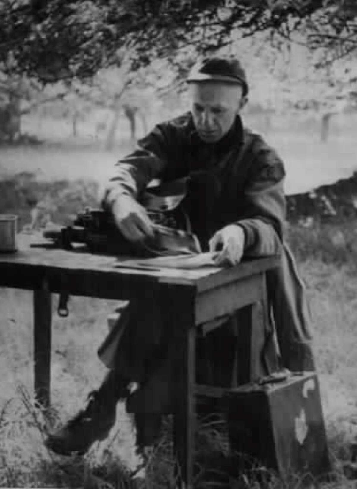 War correspondent Ernie Pyle sets up his typewriter in a field in Normandy, France in July 1944. (Associated Press archive)