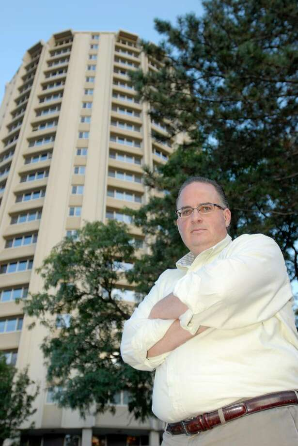 Troy City Councilman Bill Dunne stands in front of  Kennedy Towers, a popular roosting site for crows,  in Troy. (Luanne M. Ferris / Times Union) Photo: LUANNE M. FERRIS / 000005714A