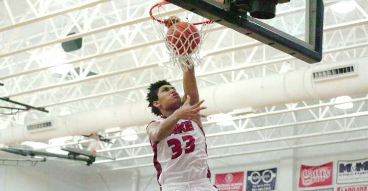 Clear Lake freshman Jeremiah Maldonado (33) slams home a left-handed dunk while Aldine Davis post Royce Hamm observes.