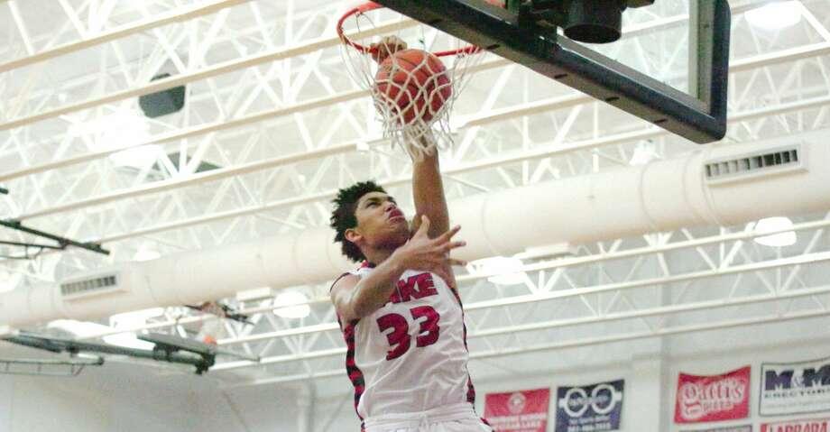Clear Lake freshman Jeremiah Maldonado (33) slams home a left-handed dunk while Aldine Davis post Royce Hamm observes. Photo: KIRK SIDES