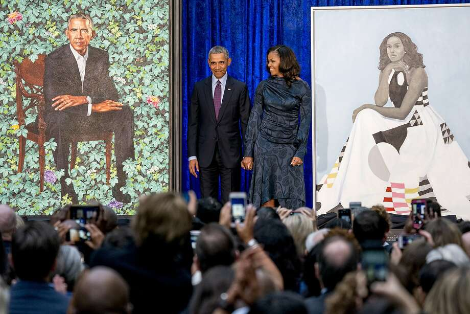 Former President Barack Obama and former first lady Michelle Obama stand together at the Smithsonian's National Portrait Gallery in Washington as their official portraits are unveiled. Photo: Andrew Harnik, Associated Press