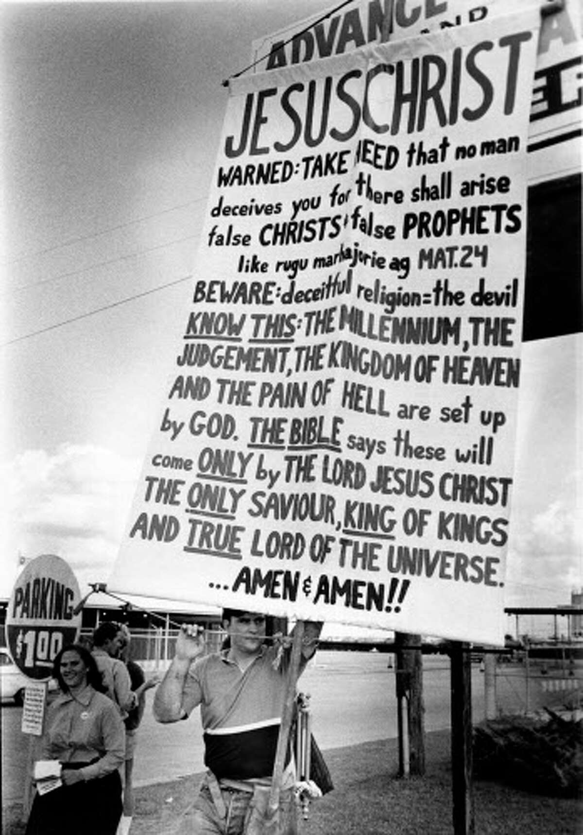 A man with a sign proclaiming his Christian beliefs outside the Astrodome during Millennium '73, an event honoring Guru Maharaj Ji, leader of the Divine Light Mission.