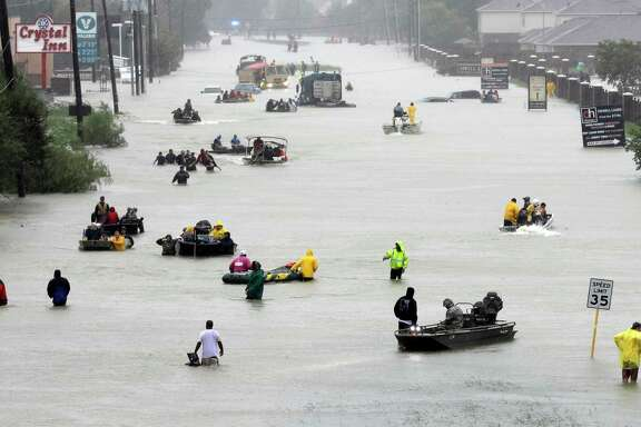 FILE - In this Aug. 28, 2017, file photo, rescue boats float on a flooded street as people are evacuated from rising floodwaters brought on by Tropical Storm Harvey in Houston. The National Hurricane Center's official report on Harvey compiles staggering numbers, starting with 68 dead and $125 billion in damage. But the really big numbers in the Thursday, Jan. 25, 2018, tally have to do with the rainfall that swamped Houston. Two places had more than five feet of rain. Eighteen different parts of Texas logged more than four feet of rain. (AP Photo/David J. Phillip, File)
