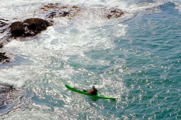 A kayaker plays in the tidal currents in a cove at Mendocino Head