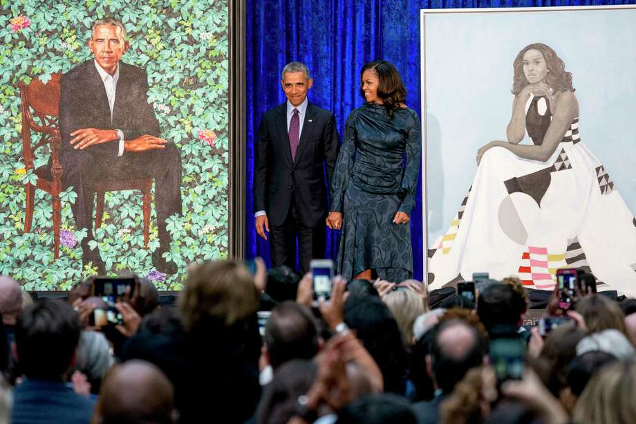 Former President Barack Obama and former first lady Michelle Obama stand on stage as their official portraits are unveiled at a ceremony at the Smithsonian's National Portrait Gallery, Monday, Feb. 12, 2018, in Washington. Barack Obama's portrait was painted by artist Kehinde Wiley, and Michelle Obama's portrait was painted by artist Amy Sherald. (AP Photo/Andrew Harnik) Photo: Andrew Harnik, Associated Press / Copyright 2018 The Associated Press. All rights reserved.