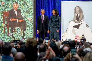 Former President Barack Obama and former first lady Michelle Obama stand on stage as their official portraits are unveiled at a ceremony at the Smithsonian's National Portrait Gallery, Monday, Feb. 12, 2018, in Washington. Barack Obama's portrait was painted by artist Kehinde Wiley, and Michelle Obama's portrait was painted by artist Amy Sherald. (AP Photo/Andrew Harnik)