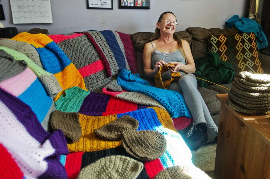 Debra Parady of Sanford poses for a portrait with items she has crocheted for veterans inside her home on Monday, Feb. 12, 2018. (Katy Kildee/kkildee@mdn.net) Photo: (Katy Kildee/kkildee@mdn.net)