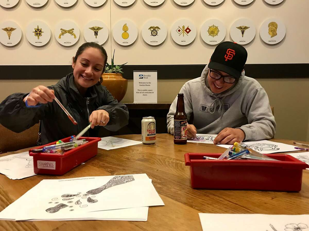 Siblings Elizabeth and Frank Juarez at work at the adult coloring station.