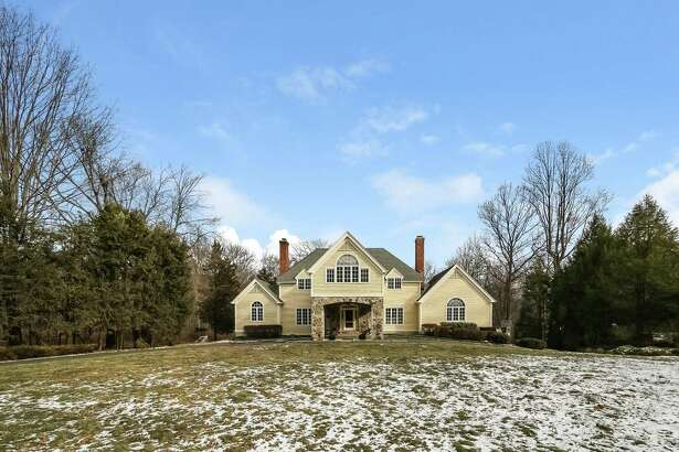 The colonial house at 95 Hickory Drive sits on a level 1.49-acre lot that adjoins the New Canaan Land Trust's 41-acre Hicks Meadows-Kelley Uplands Audubon Sanctuary.