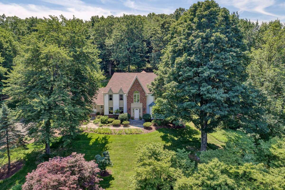 The beige colonial house at 11 Crosswicks Ridge Road sits on a two-acre level and sloping property in the Cannondale section.