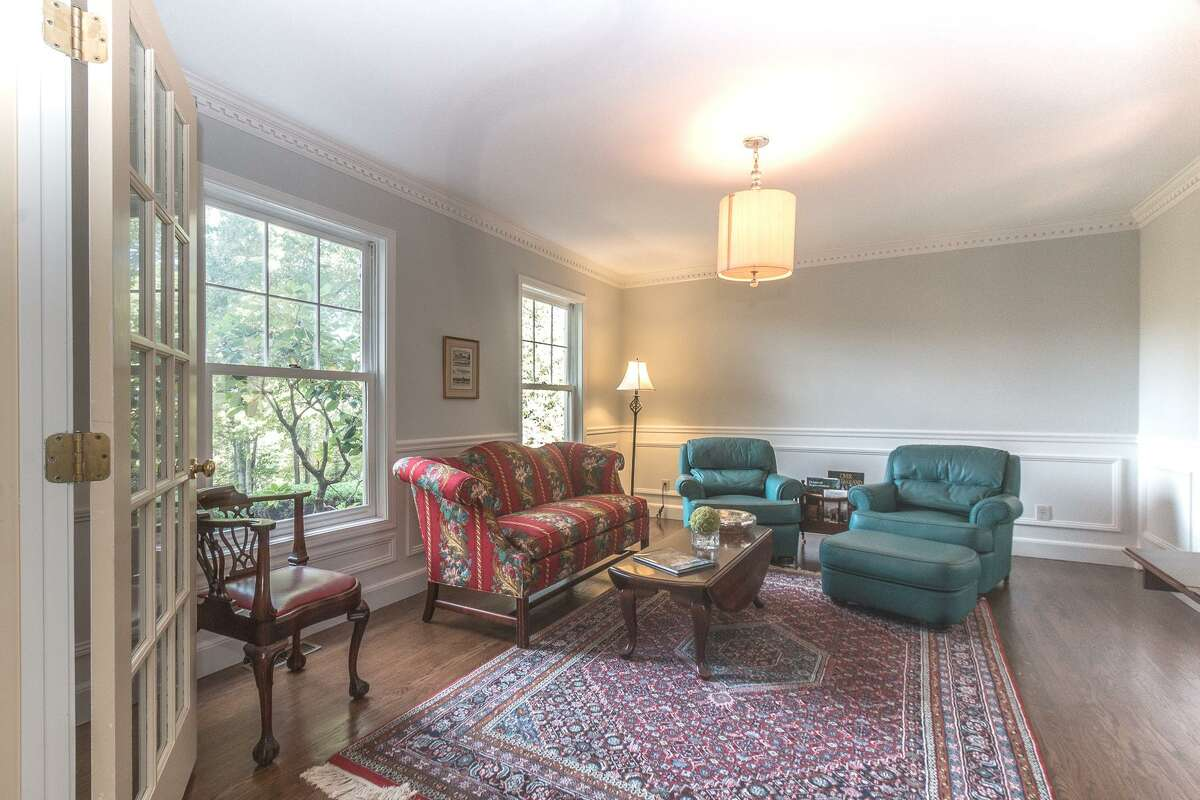 The formal living room has dentil crown molding, which is repeated in the mantel of its marble fireplace.