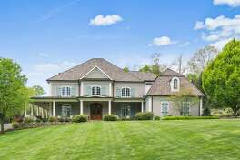 The 7,513-square-foot gray colonial house with pale blue shutters at 115 Mine Hill Road sits on a two-acre property less than three miles from town and train.
