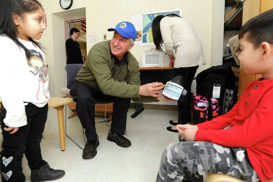 Lions Club president Sal DeMott shows children what their eyes look like after an eye-screening test at the Lathon Wider Community Center on Henry Street in Stamford, Conn. on Monday, Feb. 12, 2018. The Stamford Lions Club runs the free screening tests and so far have turned up problems with eye health in approximately one in every five children screened. Photo: Michael Cummo / Hearst Connecticut Media / Stamford Advocate