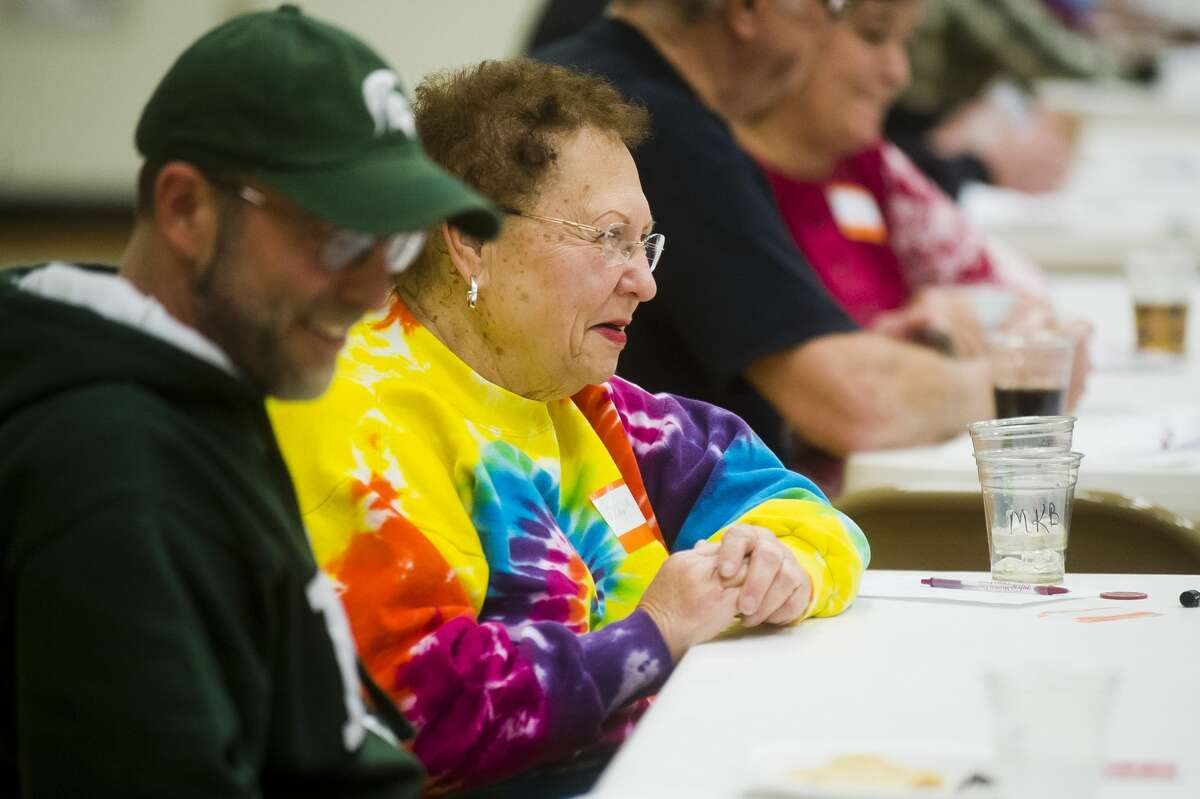 Mary Kay Brandt, center, and Todd Sloggett, left, laugh while playing euchre during a euchre night held every other month at St. Brigid Catholic Church on Ashman Street on Saturday, Feb. 10, 2018. (Katy Kildee/kkildee@mdn.net)