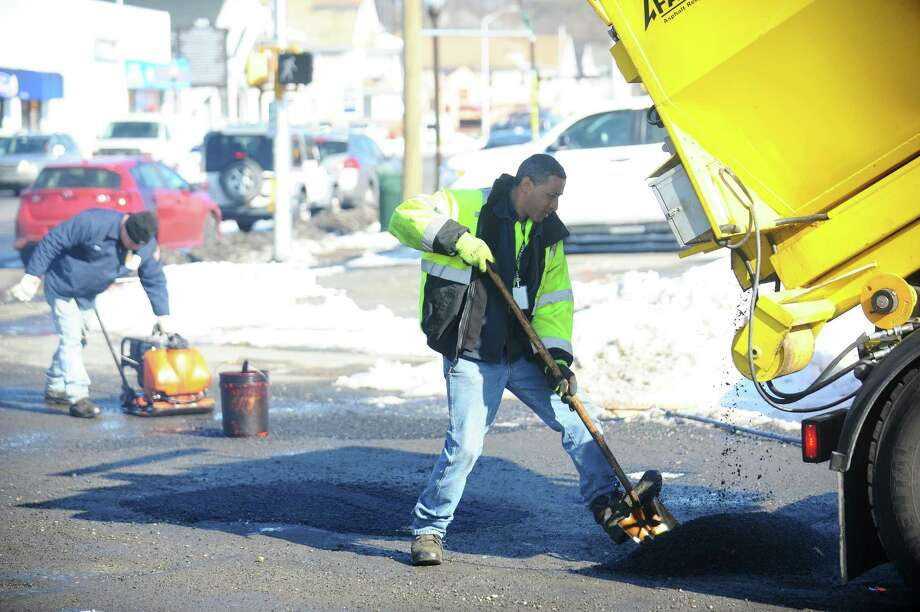 FILE PHOTO — A city crew fills potholes on Myrtle Ave., on the corner of E. Main St., in Stamford, Conn. on Tuesday, Feb. 14, 2017. Photo: Michael Cummo / Hearst Connecticut Media / Stamford Advocate