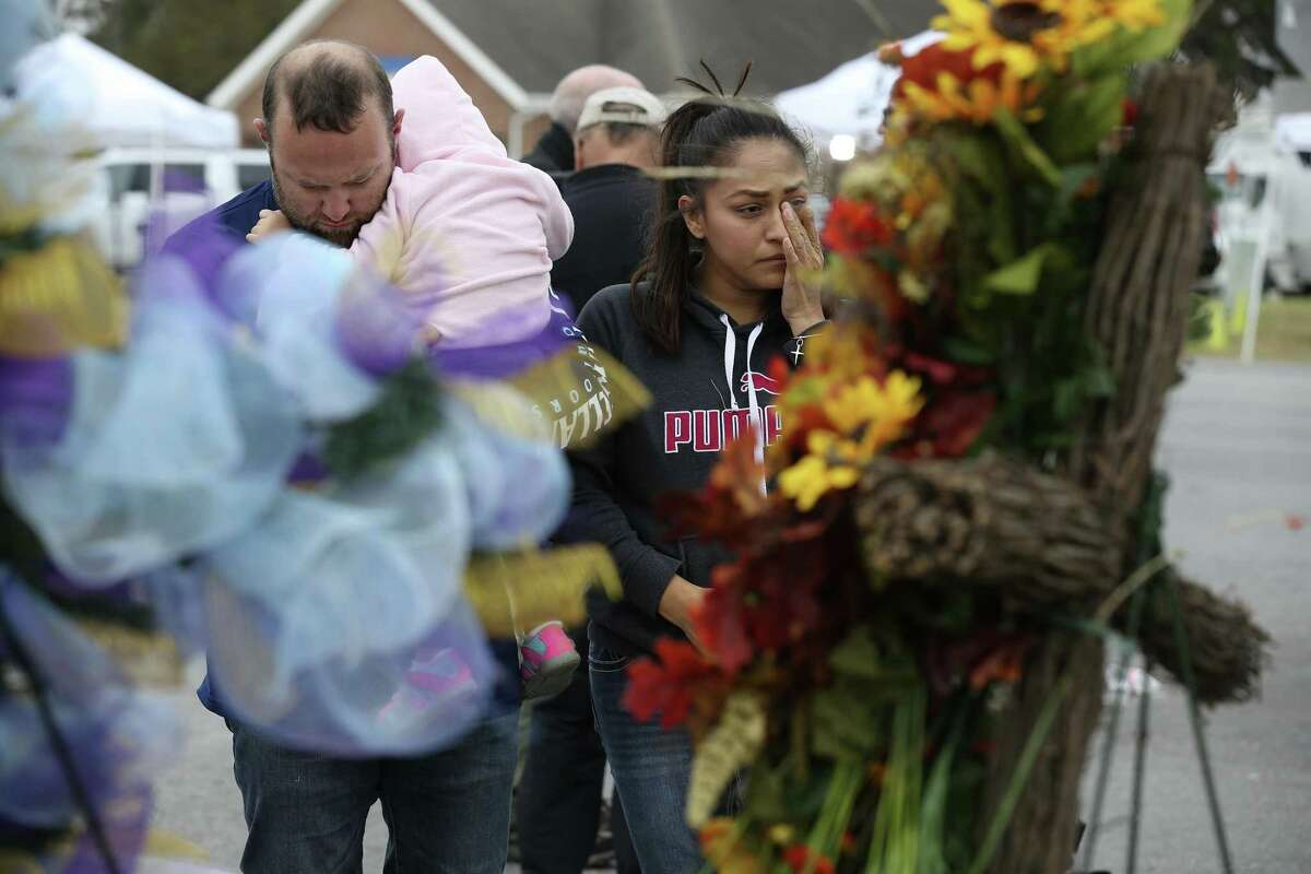 Carrying his almost 2-year-old daughter, Avery, Luke Foster and his wife, Carmen Foster, of Floresville, pay their respects at a memorial for the Sutherland Springs victims, three days after the massacre there.