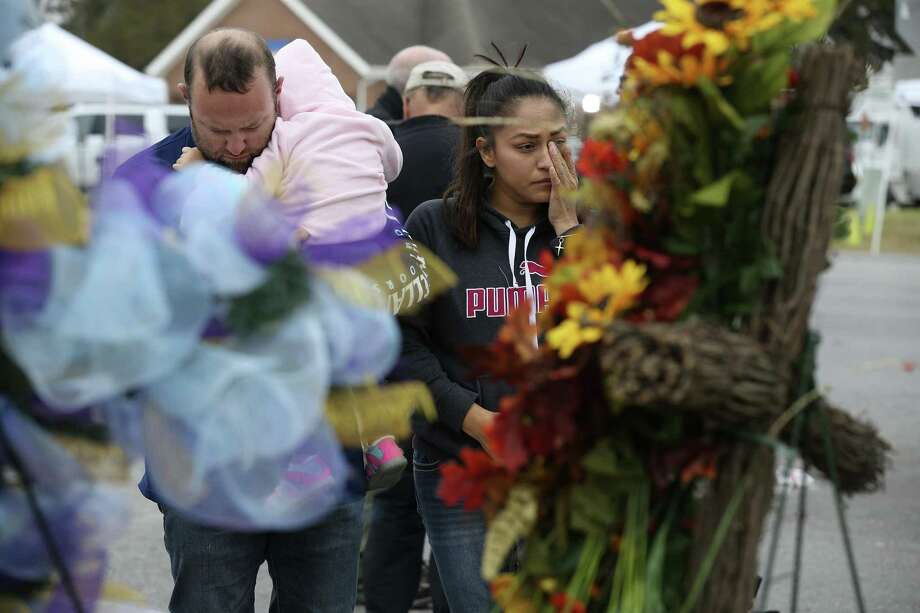 Carrying his almost 2-year-old daughter, Avery, Luke Foster and his wife, Carmen Foster, of Floresville, pay their respects at a memorial for the Sutherland Springs victims, three days after the massacre there. Photo: JERRY LARA /San Antonio Express-News / © 2017 San Antonio Express-News