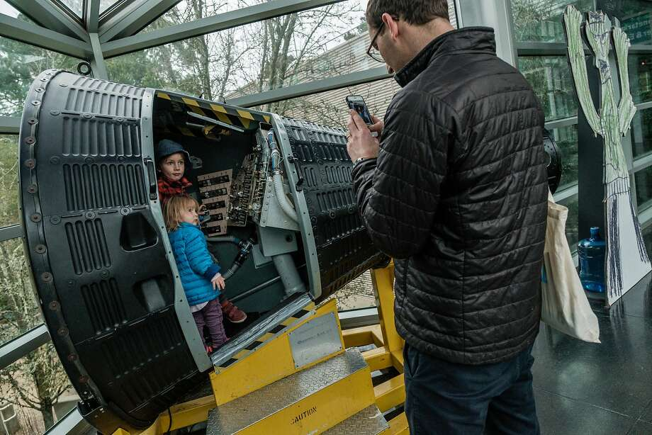 Michael Finkler of Berkeley takes a photo of his kids, Nathaniel, 5, and Uma, 2, as they interact with a display at Chabot Space & Science Center. Photo: Nick Otto, Special To The Chronicle