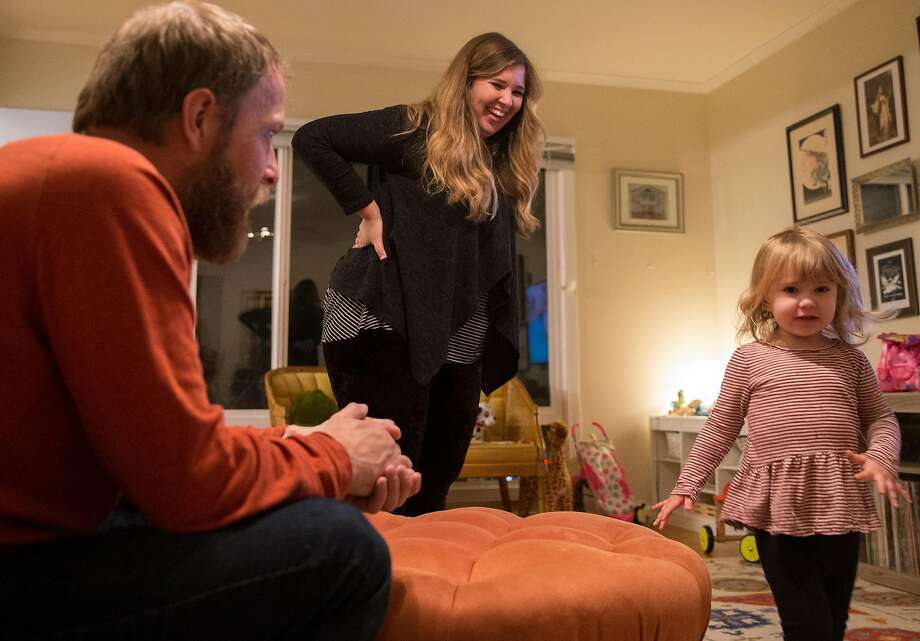 Ashley Summers laughs while watching watch daughter Alice, 2, while her husband Charlie Paulson looks on at their home Thursday, Feb. 1, 2018 in San Francisco, Calif. Photo: Jessica Christian, The Chronicle