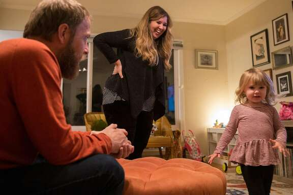 Ashley Summers laughs while watching watch daughter Alice, 2, while her husband Charlie Paulson looks on at their home Thursday, Feb. 1, 2018 in San Francisco, Calif.