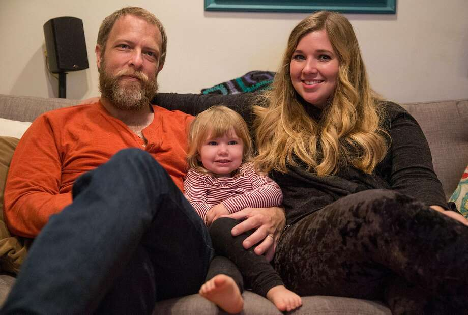 Charlie Paulson, Ashley Summers and their daughter Alice, 2, in their San Francisco living room. Photo: Jessica Christian, The Chronicle