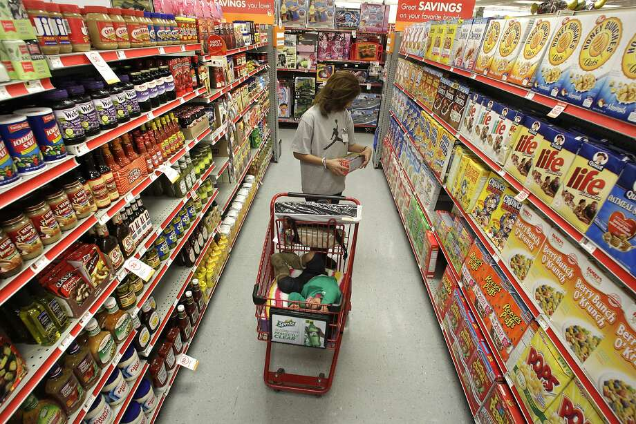 In this file photo, a woman shops through the cereal isle as her 2-year-old daughter Aaliyah Garcia catches a short nap in the shopping cart at the Family Dollar store in 2010. Photo: Tony Gutierrez, AP