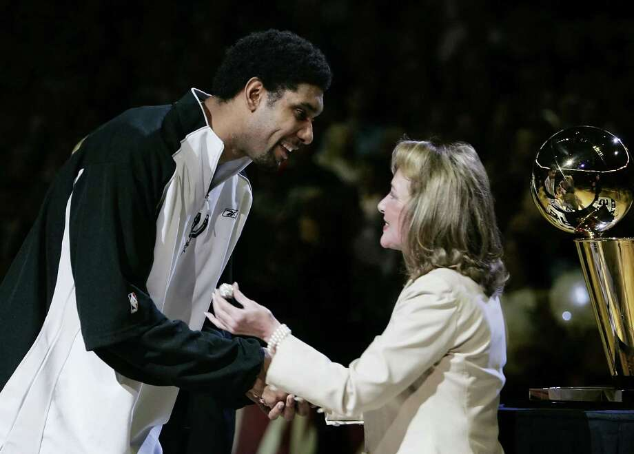 San Antonio Spurs forward Tim Duncan, left, receives his 2005 NBA championship ring from Julianna Hawn Holt, wife of team owner Peter Holt,  during a pregame ceremony before the Spurs season opener against the Denver Nuggets in San Antonio, Tuesday, Nov. 1, 2005.  The rings weigh more than two ounces of 14 karat gold with 2.55 carat weight of diamonds. (AP Photo/Eric Gay) Photo: ERIC GAY, STF / AP / AP