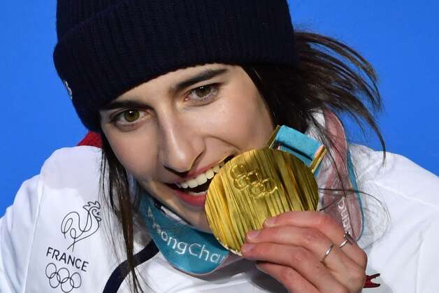 France's gold medallist Perrine Laffont bites her medal on the podium during the medal ceremony for the women's freestyle skiing moguls at the Pyeongchang Medals Plaza during the Pyeongchang 2018 Winter Olympic Games in Pyeongchang on February 12, 2018. Photo: FABRICE COFFRINI/AFP/Getty Images